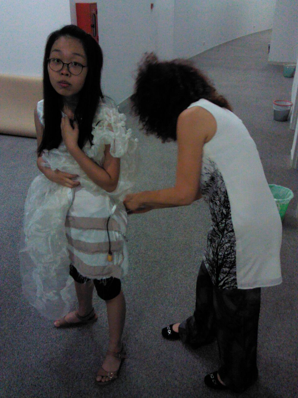 Here, Galina is helping me out with the power bank attachment to the lily pad which is located at the back of my dress.